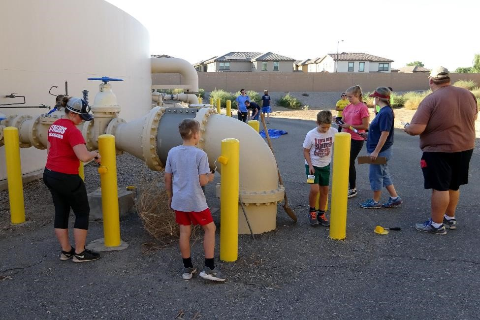 The Honey Foundation and LDS volunteers painted safety bollards and swept decomposed granite around tank at Booster Site #21.