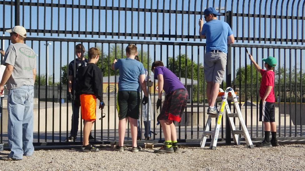 Eagle Scout candidate, L. Christensen, led LDS and Western Sky Middle School volunteers in painting the Skate Park fence.