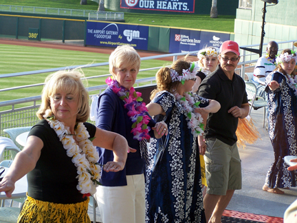 Mayor Lord (second from left) learns a Hawaiian dance.